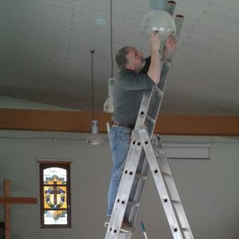 Mesner auf der Leiter
